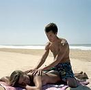 Guy massaging girl on empty beach