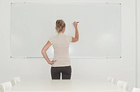 woman writing on office whiteboard