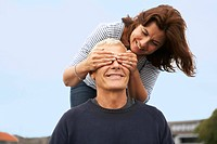 Couple, her hands over his eyes
