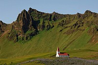 Red and white church surrounded by fields of lupins above the town of Vik, southern Iceland, Iceland, Vik