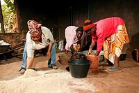 Women preparing grain for pig food, Bamenda, Cameroon, Africa