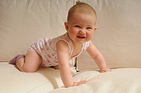 6-month-old baby crawling on a white sofa laughing
