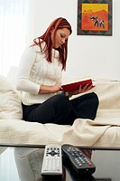 woman sits on a sofa, reading a book
