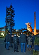 steelwork Henrichshuette at dusk with visitors during a guidance, Germany, North Rhine_Westphalia, Ruhr Area, Hattingen