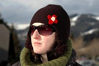 young woman with sunglasses and cap in winter