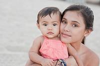 Hispanic mother hugging baby girl