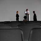 Business people talking in empty auditorium