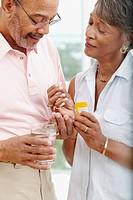 African woman helping husband take medication