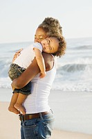 African mother holding son on beach