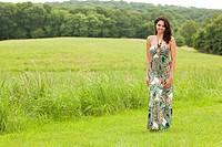 Hispanic woman in evening gown in field