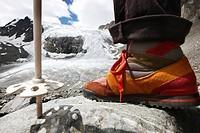 Foot and ski stock of a hiker hiking from Peiljoch alongside the Sulzen Glacier, Stubai Valley, Tyrol, Austria, Europe