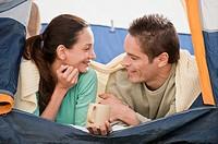 Hispanic couple laying in tent
