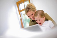 Germany, Ammersee, Diessen, Mother with daughter 6_7 using laptop, laughing, portrait