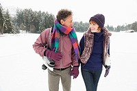 Italy, South Tyrol, Seiseralm, Couple outdoors carrying ice skates