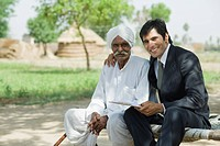 Financial advisor sitting with a farmer and smiling