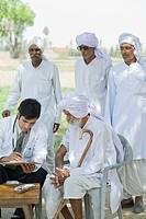 Doctor writing a prescription for a farmer