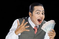 Close_up of a mime holding currency notes