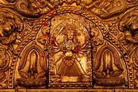 Golden, multiple-armed god figure on a door in the historic centre of Bhaktapur, Nepal, Asia