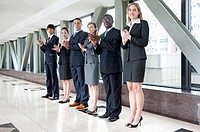 Business people standing in a row and clapping together