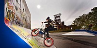 BMX_cyclists in front of old coal mine Consolidation, Germany, North Rhine_Westphalia, Ruhr Area, Gelsenkirchen