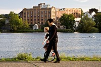 woman with child on a an unicycle at Ruhr river in Hattingen with Birschel mill in background, Germany, North Rhine_Westphalia, Ruhr Area, Hattingen