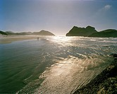 People in the shallow water at Wharariki Beach, northwest coast, South Island, New Zealand