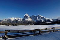 Wooden fence at snow covered Alpe di Siusi under blue sky, Dolomites, South Tyrol, Italy, Europe