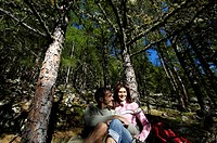 Young couple resting in a sunlit coniferous forest, Schnals valley, Val Venosta, South Tyrol, Italy, Europe