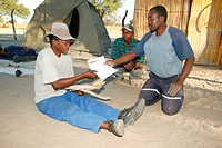 Traditional healer's patient being given his prescription for medicinal herbs, Sehitwa, Botswana, Africa