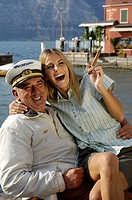 Laughing woman holding a cigar sitting on the lap of a man wearing a captain´s cap, Garda lake, Italy, Euorpe