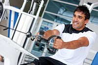 man at the gym doing exercise on a machine with weight