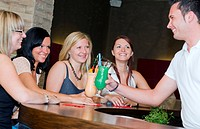 four young women sitting at the bar making goo_goo eyes at young barkeeper serving them cocktails