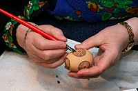Femal hands painting an easter egg with beeswax for dyeing in traditional Hessian batik technique