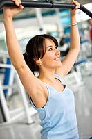 young woman doing back exercise at a machine in the gym
