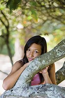 Girl leaning on tree