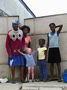 albino girl standing at gate to compound with 4 female members of her family, Haiti, Province de l´Ouest, Kenskoff, Port_Au_Prince