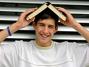 Male teen with a book on his head