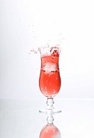 Ice cube falling in a glass of red liquid, juice, cocktail