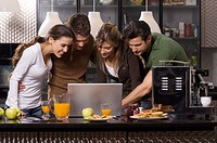 young women and men with notebook in kitchen
