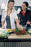 two young women in kitchen, preparing the dinner together