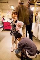 Boy tying the shoelaces for his sister  Kolaportid flea market  Downtown Reykjavik, Southwest Iceland