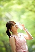 Japan, Osaka Prefecture, Woman holding water bottle, looking away, smiling