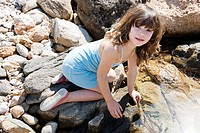 A girl kneeling next to a rock pool