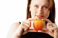 Closeup portrait of a young pretty woman holding a red apple in her hand, isolated over white background