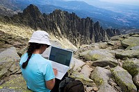 Woman on the summit of La Mira 2 341 m working with a portable computer  Mountains of the Sierra de Gredos National Park  At the bottom of the image t...