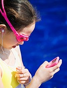 Young girl at poolside listening to music player