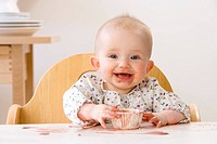 Messy baby girl in high chair eating