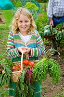 Girl picking vegetables in garden