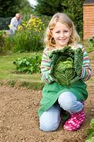 Girl holding cabbage in garden
