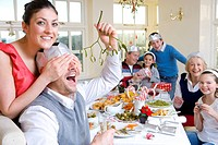 Woman covering eyes of man with mistletoe at dinner table